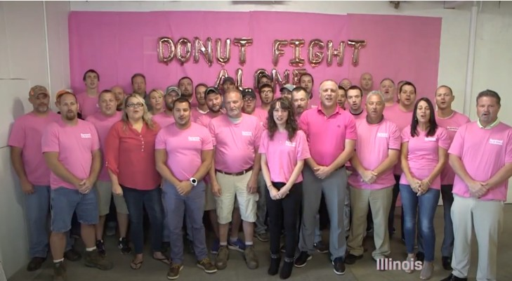 group of people all wearing pink shirts