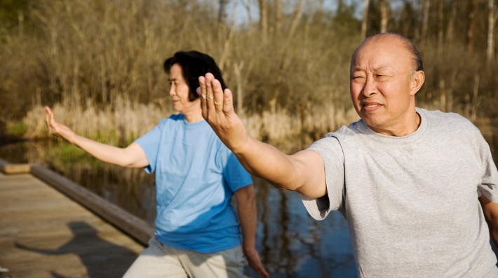 senior Asian couple doing tai chi outside