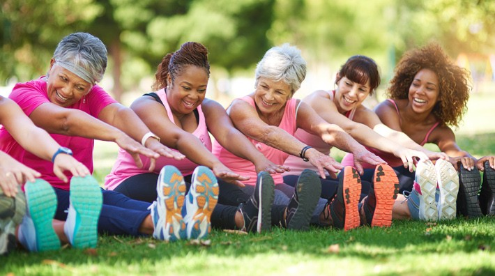 diverse group of women stretching outside before exercise