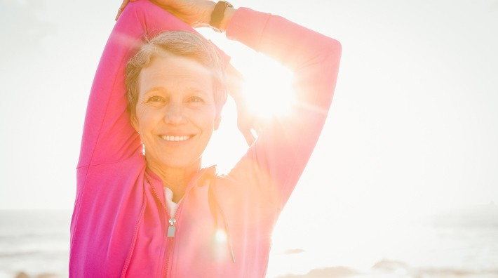 smiling middle aged woman stretches on sunny beach before exercise