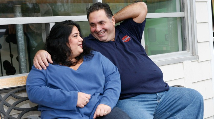 happy overweight couple sitting on bench outdoors