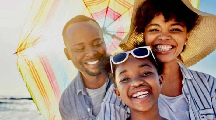 close up of smiling mom, dad and young daughter under umbrella at the beach with sun shining in background